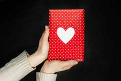 Hand holding red gift isolated on black. Hand holding red gift with heart isolated on black Stock Photography