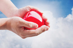 Hand holding red hart on blue sky and white clouds, with bright light Royalty Free Stock Photos