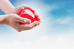Hand holding red hart on blue sky and white clouds, with bright light Royalty Free Stock Image