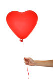 Hand holding a red heart balloon isolated on a white Stock Image