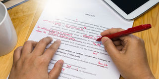 Hand holding red pen over proofreading text. On table stock photography