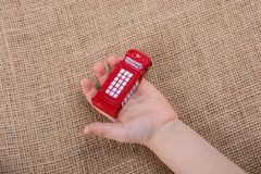 Hand holding a red phone booth. Hand holding a phone booth on a brown background Stock Image