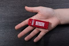 Hand holding a red phone booth. Hand holding a phone booth on a dark background Stock Photos