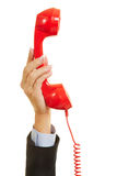 Hand holding red phone for emergency call. Hand of a woman holding a red phone for emergency call Royalty Free Stock Photos