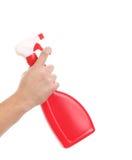 Hand holding red plastic spray bottle. Stock Image