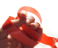 Hand holding red ribbon. Hand holding a red ribbon isolated against a white background Royalty Free Stock Images