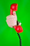 Hand holding red telephone Stock Photography