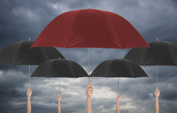 Hand holding red umbrella different among black umbella. Stock Photo
