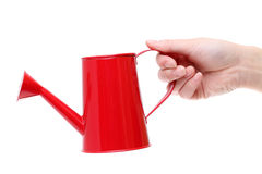Hand holding red watering can Stock Images