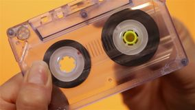 Hand holding and reeling transparent compact audio cassette. Tape - on orange background, closeup stock video