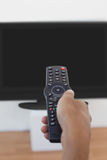 Hand holding remote and changing channel Stock Image