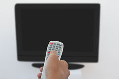 Hand holding remote and changing channel Stock Photos
