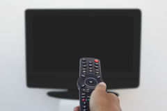 Hand holding remote and changing channel Royalty Free Stock Photos