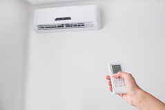 Hand holding remote control for air conditioner on white wall. Hand holding remote control, adjusting temperature of air conditioner mounted on a white wall Royalty Free Stock Image