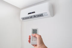 Hand holding remote control for air conditioner on white wall. Stock Photos