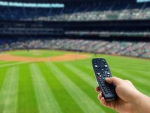 Hand holding remote control on baseball match TV Stock Image