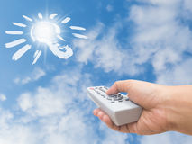 Hand holding remote control direct to sunlight and bulb sign Stock Photo