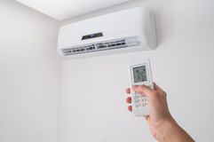 Free Hand Holding Remote Control For Air Conditioner On White Wall. Royalty Free Stock Photo - 96289575