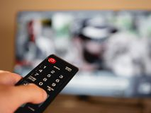 Hand holding remote control in front of television stock photo