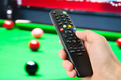 Hand holding remote control in front of tv. Closeup royalty free stock image