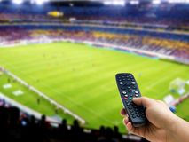 Hand holding remote control on soccer or football match TV. Or television royalty free stock images