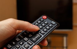Hand holding remote control for television, choosing channel in TV Stock Photos