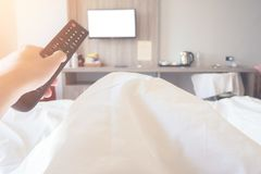 Hand holding remote control television ob bed in bedroom close up stock images
