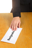 Hand holding resignation letter on the desk of the boss. Stock Photography