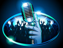 Hand holding Retro Mic/ Microphone in front of huge silhouetted crowd Stock Photo