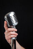 Hand holding a retro microphone Royalty Free Stock Photos