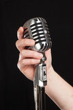 Hand holding a retro microphone Stock Image