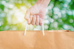 Hand holding reuse paper bag, on green Bokeh and bright yellow light background Stock Photo