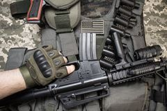 Hand holding a rifle on tactical equipment. Upper view photo of hand in tactical gloves holding a rifle on military tactacal bulletproof vest, cartrige belt Royalty Free Stock Image