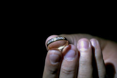 Hand holding a ring with black background. Hand holding a ring with black and dark background Royalty Free Stock Photo