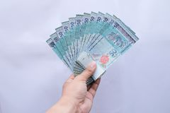 Hand holding a 50 Ringgit Malaysia money on a white background stock images