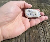 Hand holding a rock with inspirational sentiment. Hand holding rock with inscription against a rough wood background Royalty Free Stock Photos