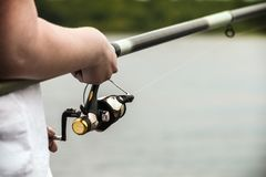 Hand holding the rod and reel stock photography