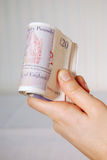 Hand holding a roll of twenty pound notes Royalty Free Stock Image