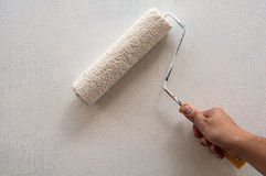 Hand holding rolling paint brush. Wall painting royalty free stock images