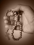 Hand holding rosary beads Royalty Free Stock Photography