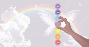 Hand holding Rose Quartz heart. And the seven chakras Stock Image