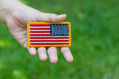 Hand holding Rounded American flag patch Royalty Free Stock Images