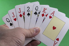 Hand holding a royal flush hearts Stock Images