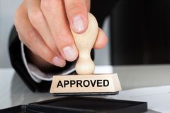 Hand holding rubber stamp with approved sign. Closeup of hand holding rubber stamp with Approved sign at table in office stock photos