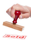 Hand holding a rubber stamp with the word Sold Royalty Free Stock Images