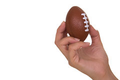 Hand holding rugby ball. Feminine hand holding miniaturized rubber rugby ball over white background stock photo