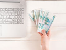 Hand holding russian rubles near laptop. On white wooden background. Top view or flat lay. Finance and earning concept Royalty Free Stock Photos