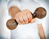 Hand holding rusty dumbbell Royalty Free Stock Image