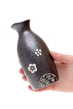 Hand holding sake bottle Stock Photo