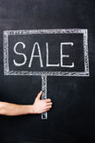 Hand holding sale sign drawn on blackboard Royalty Free Stock Image